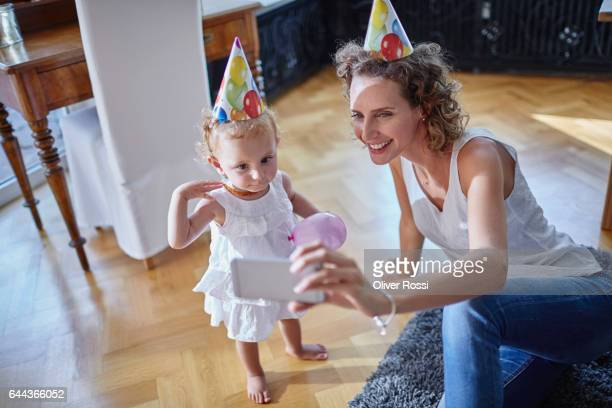 Happy mother with baby girl wearing party hats taking a selfie at home