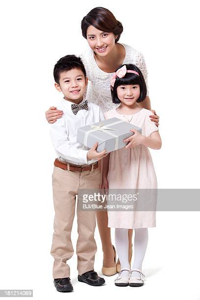 Happy mother with daughter and son holding gift