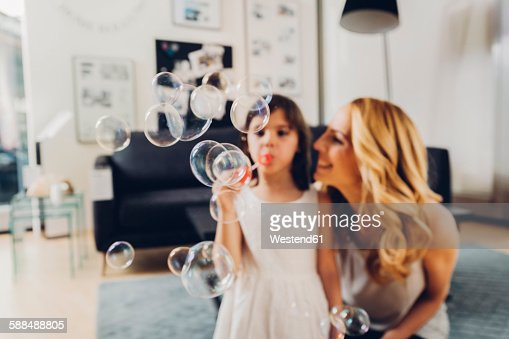 Happy mother with daughter at home blowing soap bubbles