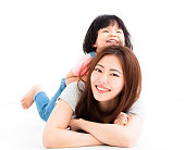 happy mother with little girl playing on the floor