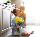 happy mother's day! baby son congratulates mother on holiday and gives flowers