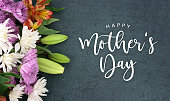 Spring season still life with Happy Mother's Day calligraphy holiday script over dark blackboard background with beautiful colorful white, pink, orange, purple and green flower blossom bouquet