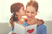 Happy mother's day! Child daughter congratulates moms and gives her a