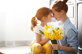 happy mother's day! child daughter congratulates mother and gives a bouquet of flowers to narcissus and gift