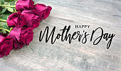 Happy Mother's Day Script with Bright Pink Roses Over Wood Background