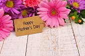 Happy Mothers Day tag close up among a bouquet of flowers over a white wood background