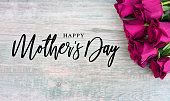 Happy Mother's Day Text with Bright Pink Roses Over Wood Background
