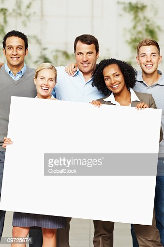 Happy multi ethnic business group holding a billboard : Stock Photo
