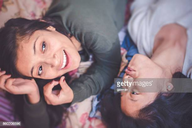 Happy multi ethnic female friends together in dorm room.