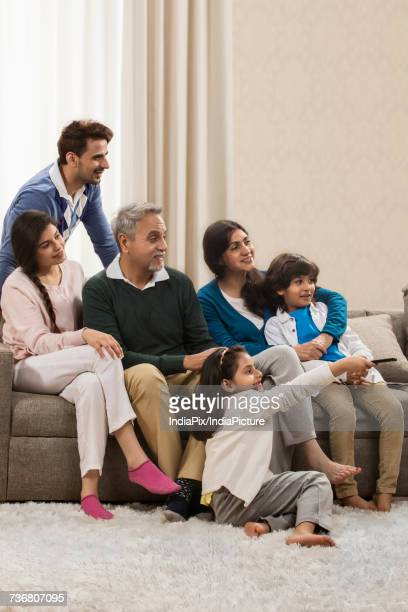 Happy multi generation family watching television in living room
