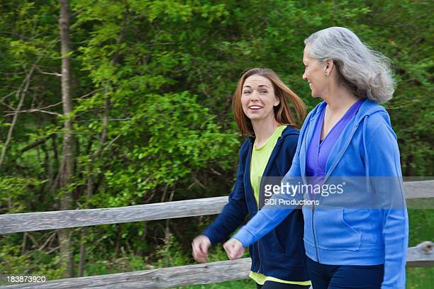 Happy Multi Generational Women Talking While Exercising Outside