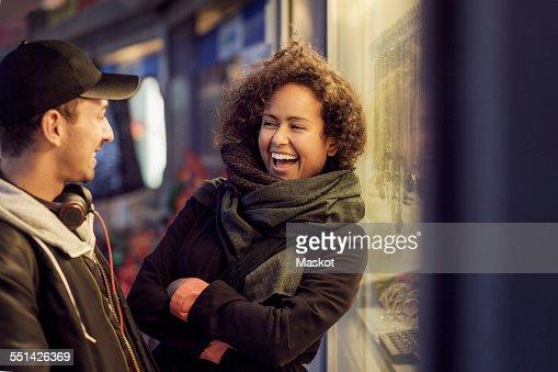 Happy multi-ethnic couple outside store at dusk