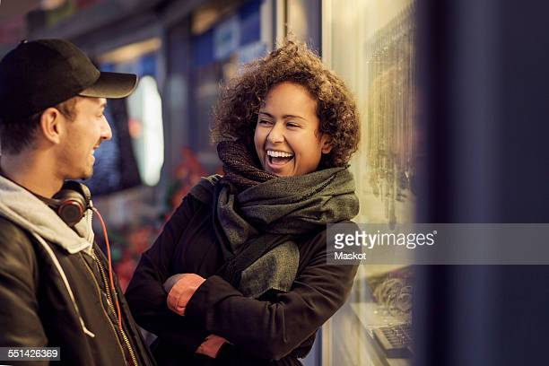 Happy multi-ethnic couple outside store at dusk