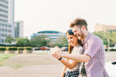 Happy multiethnic couple taking selfie during sunset in the city, fun and smiling, love or gadget technology concept