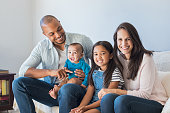 Portrait of happy multiethnic family sitting on sofa at home. Smiling couple with kids sitting on couch and looking at camera. Black father and latin woman with daughter sitting on couch and having fu