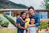 Happy multi-ethnic family outside house