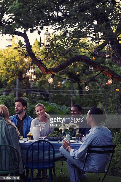 Happy multi-ethnic friends sitting at outdoor food table during evening party