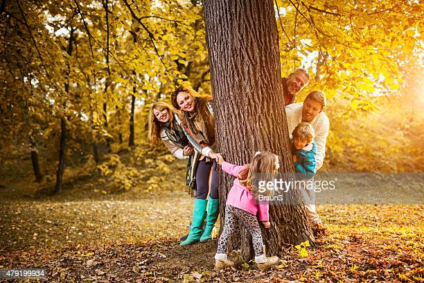 Happy multi-generation family playing around the tree in nature.