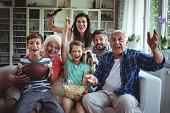 Happy multi-generation family watching soccer match on television in living room at home