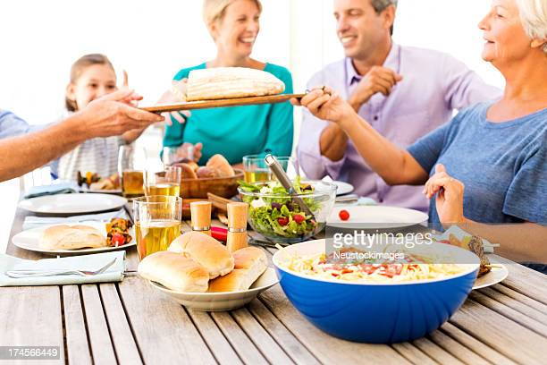 Happy Multigenerational Family Passing Bread At Patio Table