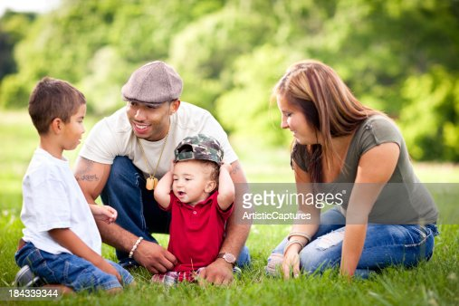 Happy, Multiracial Family Sitting Together Outside During Summer