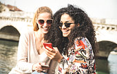 Happy multiracial girlfriends having fun outddors with mobile smart phone - Friendship concept with girls at spring break travel - Modern female lifestyle with women best friends - Bright filter tone