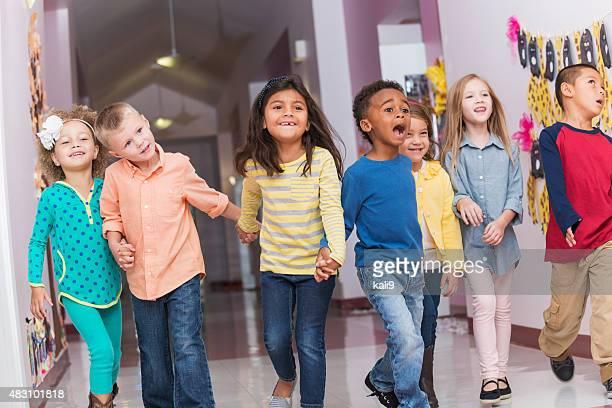 Heureux multi-ethnique de l'école à pied au hall