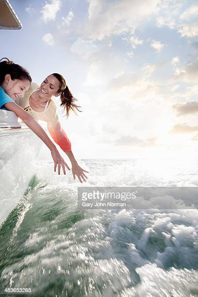 happy mum and daughter reaching into sea from boat