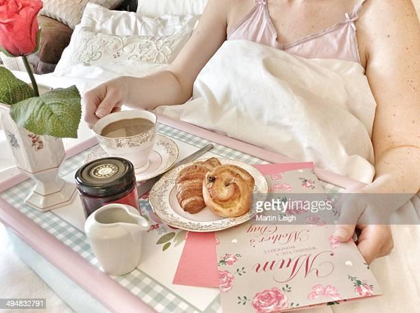 Happy mum enjoying breakfast in bed on mothers day