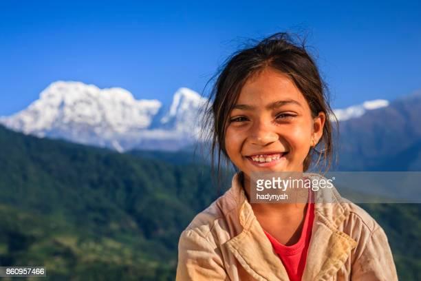 Happy Nepali little girl, Annapurna Range on background