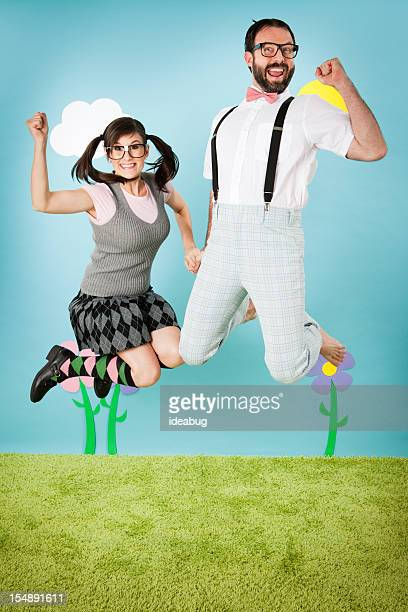 Heureux Nerd Couple tenant les mains et sauter avec enthousiasme