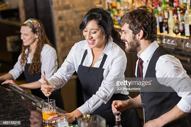 Happy new employee learning to make mixed drinks in bar