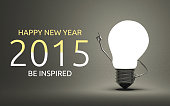 Happy New Year 2015 and be inspired greeting card, light bulb character in moment of insight standing on gray background, 3d render