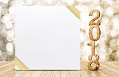 Happy new year 2018 with blank white greeting card with gold ribbon in perspective room at sparkling bokeh wall and wooden plank floor,leave space for display of design.