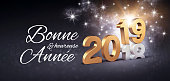 Greetings in French and New Year date number 2019 colored in gold, above ending year 2018, glittering on a festive black background - 3D illustration