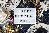 Happy new year 2019 on light box with party cup,party blower,tinsel,confetti.Fun Celebrate holiday party time table top view