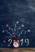 New Year 2019. Orange alarm clock on a wood shelf in front of empty blackboard. There is the number 2019 and confetti with stars drawn with chalk, the clock is replacing the zero