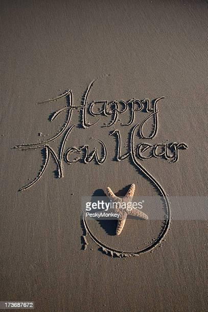 Heureuse nouvelle année Message sur sable foncé avec une étoile de mer