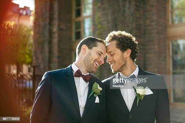 Happy newlywed gay couple standing outdoors