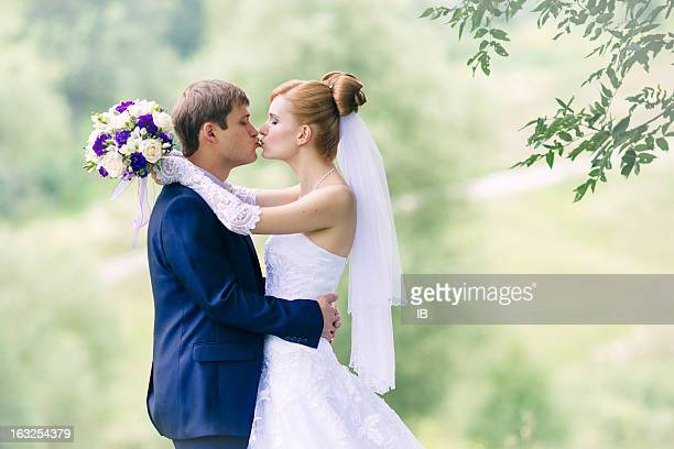 Happy newlyweds among the foliage. Tenderness, fun, love, beauty