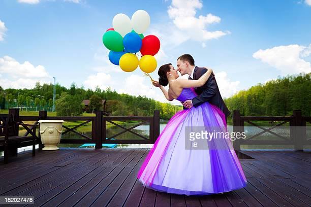 Sposi felici dal lago con palloncini colorati