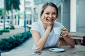 Closeup portrait of smiling young beautiful woman looking at camera, leaning head on hand and drinking coffee at cafe table outdoors with street view in background. Front view.