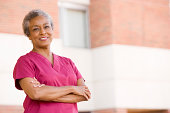 Nurse Standing Outside A Hospital On Her Own Smiling At Camera