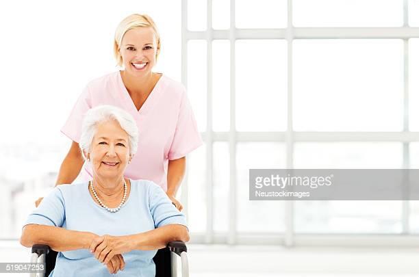 Heureux Infirmière en poussant Senior femme en fauteuil roulant