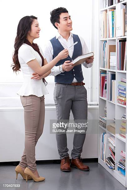 Happy office workers talking in front of book shelf