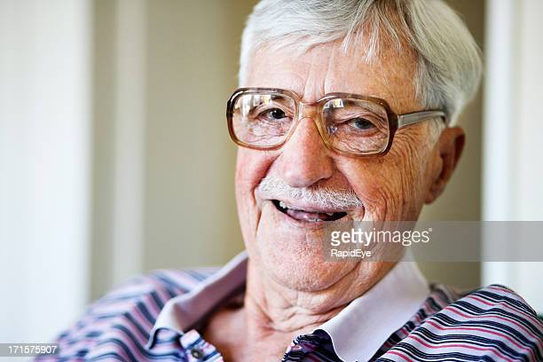 Happy old man in spectacles laughs