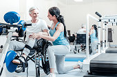 Helping others. Happy smiling old grey-haired man sitting in a wheelchair while a content young dark-haired female trainer smiling and standing near him and a training device in front of them