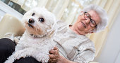 Happy old woman enjoying spending time with dog at home.