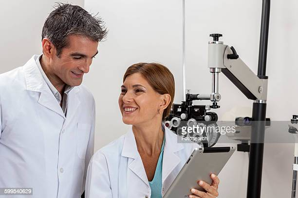Happy ophthalmologists looking at tablet