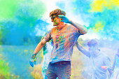 Happy positive smiling fun man wearing blue sunglasses all stained with colorful paint celebrating Holi festival party with friends. On color dust smoke powder cloud background in park field outdoor.
